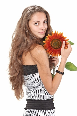 Young beautiful girl with long hairs holding sunflower on white photo