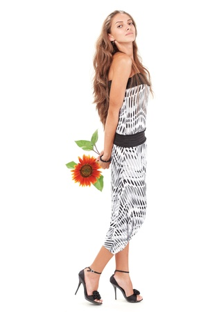 Young beautiful lady in harem pants with sunflower full-length studio portrait on white photo