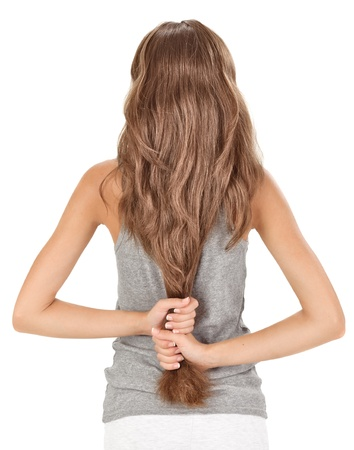 Brunette lady holding long hairs, view from back side isolated on white photo
