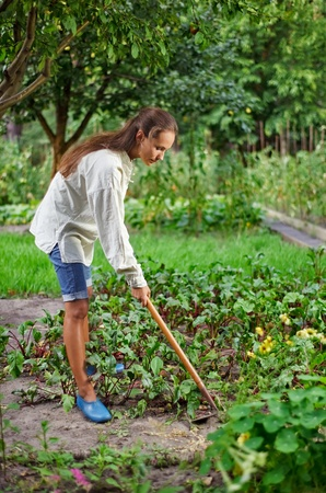 hoe: Young woman with hoe working in the garden bed