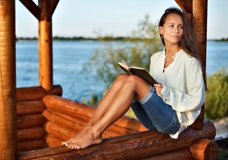 tuinhuis: Jonge nadenkend dame met boek in verleden op zons ondergang Stockfoto