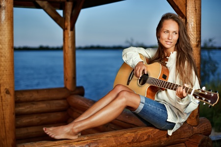 Young woman playing guitar in summerhouse on sunset photo