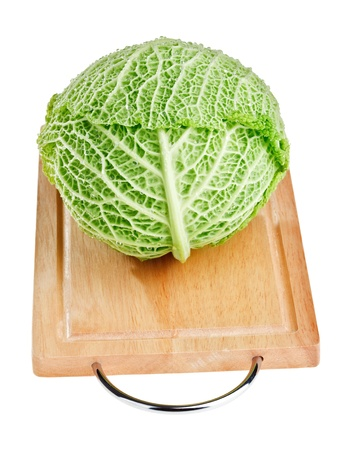 Fresh green cabbage head on wooden chopping board over white background Stock Photo - 8438692