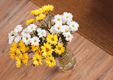 Bouquet of chamomile flowers in glass vase on wooden floor Stock Photo - 8547644
