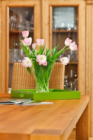 Bouquet of pink tulips flowers in glass vase on wooden table photo