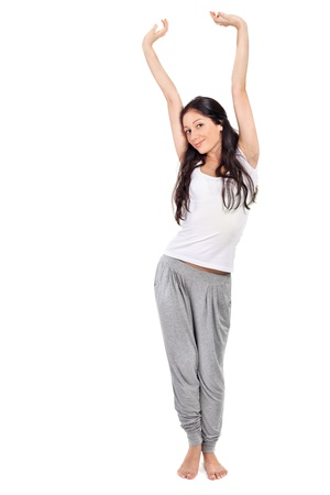 Young beautiful brunette lady stretching after awaking Stock Photo