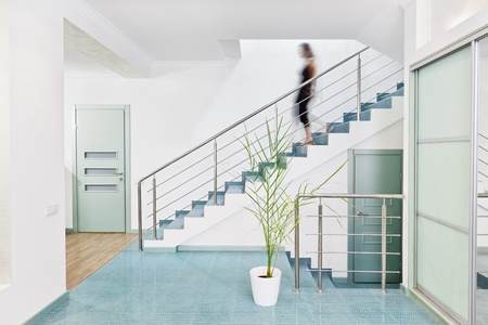 Modern hall interior in minimalism style with blurred person moving downstairs photo