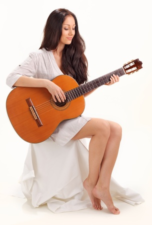 Young beautiful smiling brunette lady in white chemise playing acoustic guitar Stock Photo - 8547280