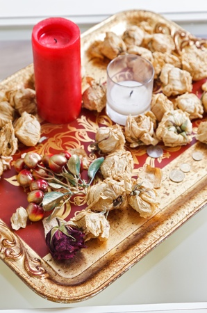 Still life with red candle and dried rose flowers on a gold tray Stock Photo - 8566959