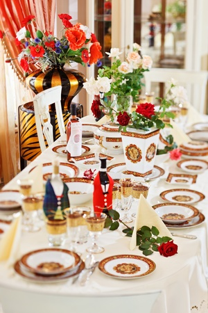 Luxuriant table appointments with red  china porcelain and rose flowers. Shot is made with tilt-and-shift lens and has diagonal focus plane and extremely shallow depth of field Stock Photo - 8566965