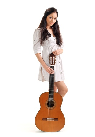 Young beautiful brunette girl in white chemise with acoustic guitar photo
