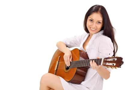 Young beautiful smiling brunette lady in white chemise playing acoustic guitar photo