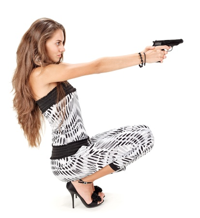 Young woman in harem pants aiming with black pistol on white photo