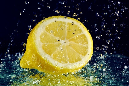 Half of lemon with stopped motion water drops on black photo