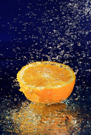 Half of orange with stopped motion water drops on deep blue Stock Photo - 8679196