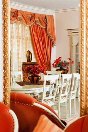 Part of modern art deco style dining room interior with striped vase and red flowers reflected in mirror with golden frame Stock Photo - 8679208