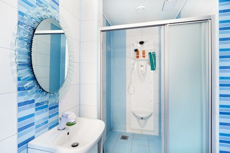 Modern blue bathroom interior with round mirror and shower cubicle photo