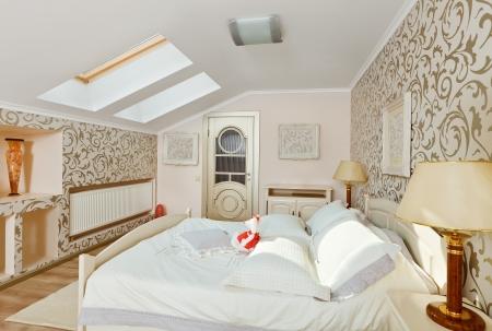attic: Modern art deco style bedroom interior in light beige colors on loft room