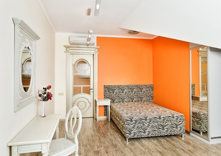 Modern art deco style bedroom in bright orange colors with zebra patterned bed on loft room Stock Photo - 8679209