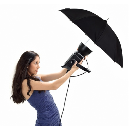Young pretty lady in blue dress holding studio flash with umbrella isolated on white Stock Photo - 8679236