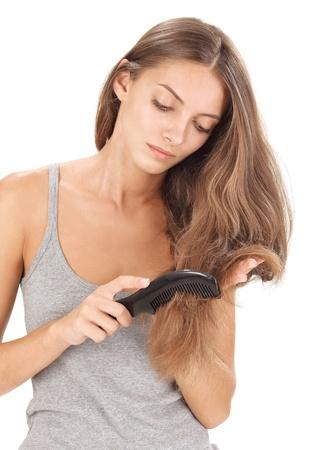 Jeune femme belle brunette peignage longs poils sur fond blanc Banque d'images