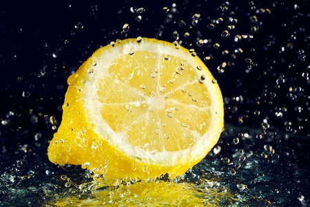 Half of lemon with stopped motion water drops on black Stock Photo - 8771314
