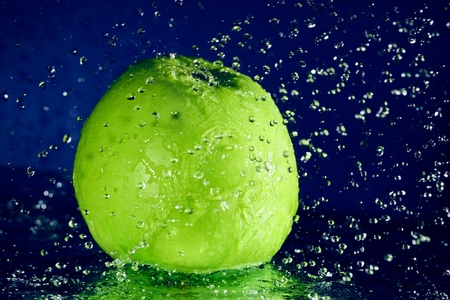 Whole green apple with stopped motion water drops on deep blue Stock Photo - 8771315