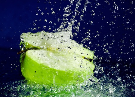 Half of green apple with stopped motion water drops on deep blue photo