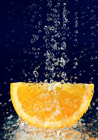 Slice of orange with stopped motion water drops on deep blue Stock Photo - 8771310