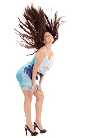 Young pretty lady in blue dress with long hairs flying upwards, studio portrait on white photo