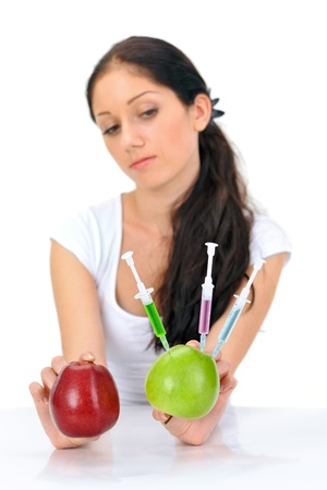 Young attractive woman holding GMO apple with three syringe on white photo