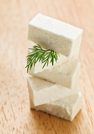 Feta cheese cubes with dill twig on wooden chopping board