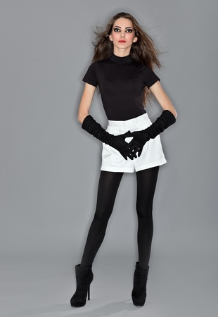 Young beautiful woman in black combi dress, white shorts and velvet gloves, ring flash studio portrait photo