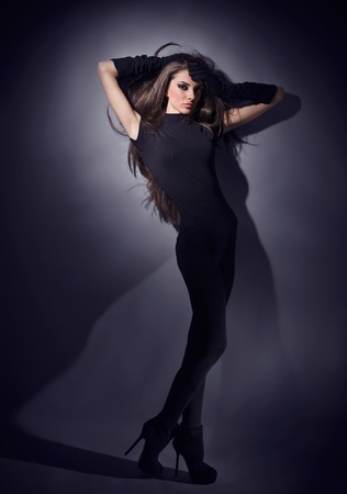 Young slim glamour lady with long hairs dressed in black combi dress, dark key studio portrait Stock Photo - 8984591