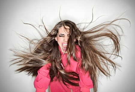 Screaming furious aggressive brunette woman with flying long hairs, ring flash studio portrait on white