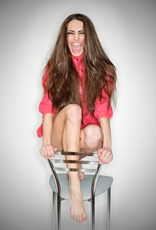 hysterics: Screaming aggressive emotion woman in pink blouse with long hairs, ring flash studio portrait on white