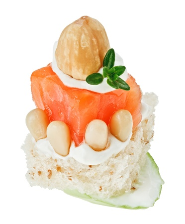 Elegant canape with salmon roll, toast, thyme twig and hazel nut isolated on white Stock Photo - 8984652