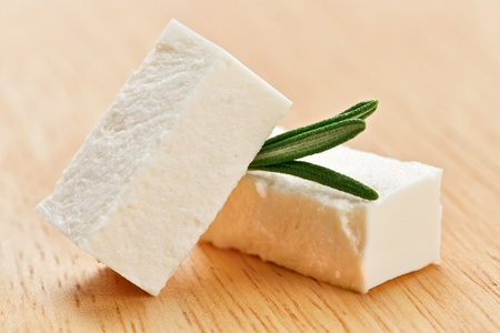 Feta cheese cubes with rosemary twig on wooden chopping board photo