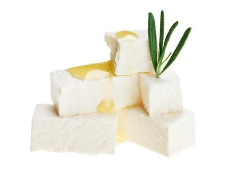 queso: Cubos de queso feta con gotas rama y aceite de Romero, aislados en blanco Foto de archivo