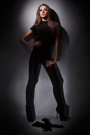 Young slim glamour lady with long hairs dressed in black combi dress, dark key studio portrait photo