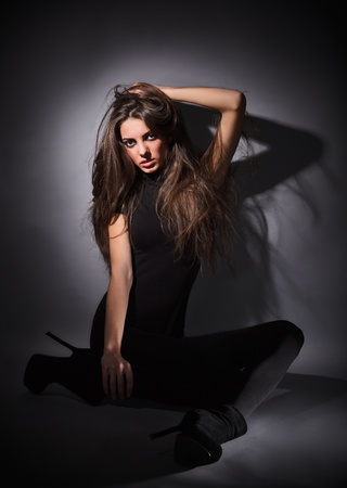 Young slim glamour lady with long hairs dressed in black combi dress sitting on the floor, dark key studio portrait photo