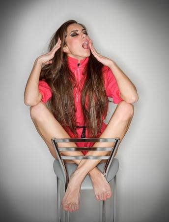 mani incrociate: Sbadigliando sonnolenta carina donna in camicia rosa con peli lunghi, ritratto di ring flash studio su bianco Archivio Fotografico