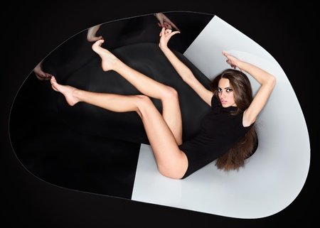 Young slim beautiful lady dressed in black dress in abstract plastic tube, ring flash fashion portrait photo