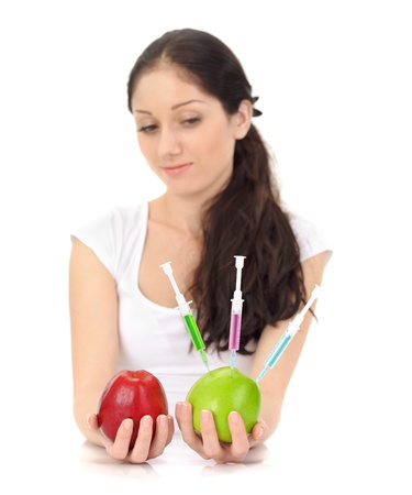 Young attractive lady holding GMO apple with three syringe on white photo