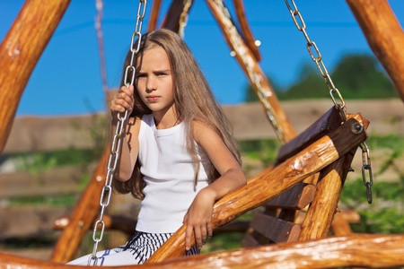 Serious little girl with blond long hair sitting on wooden chain swing in rural playground Stock Photo - 9295783