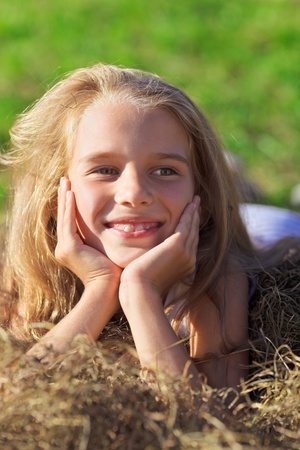 Cute little girl with blond hair laying in hay heap on green lawn photo