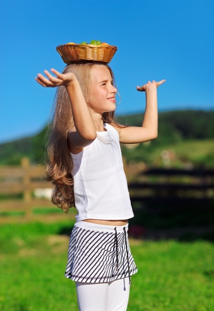 Cute little girl with long blond hair carrying fruit basket on head Stock Photo - 9295778