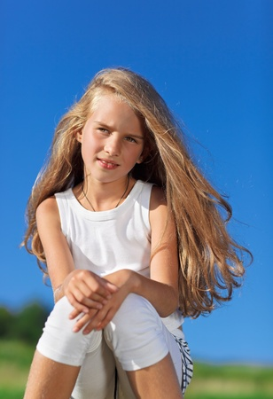Cute little girl with blond long hair outdoor portrait in front of  blue sky Stock Photo - 9295779