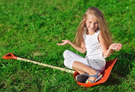 Cute little girl with blond long hair sitting on red plastic shovel over green grass lawn Stock Photo - 9287426