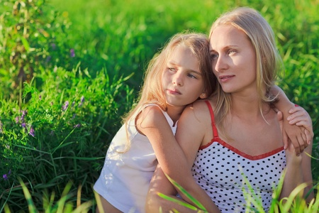 Beautiful mother and daughter sitting on green lush grass meadow in sunset sun beams Stock Photo - 9287441
